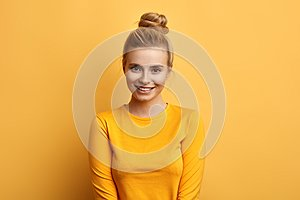 Gorgeous attactive female model posing to the camear over yellow background