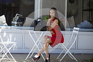 Girl sitting on the chair in chic shoes with a stylish black bag and red dress