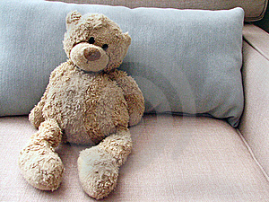 Stuffed Toy Teddy Bear on Couch with Pillow