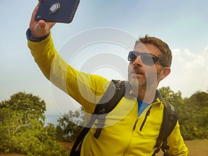 Young happy and attractive sporty hiker man with trekking backpack hiking at mountain taking selfie enjoying travel getaway