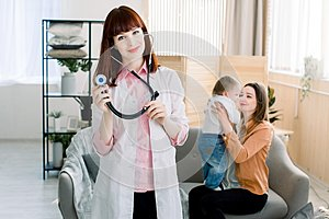 Medicine, healthcare, pediatry and people concept - Attractive female doctor in front of woman with baby, doctor`s visit