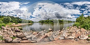 Full spherical seamless hdri panorama 360 degrees angle view on rocky shore of huge river in sunny summer day and windy weather