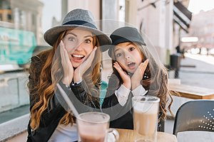 Two amazing girls in trendy hats posing with funny face expression during lunch in street restaurant in sunny day. Young