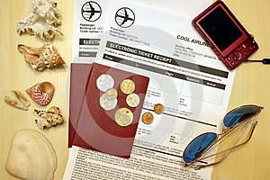 Composition from two passports with air tickets, compact camera, sunglasses, sea shells and foreign coins