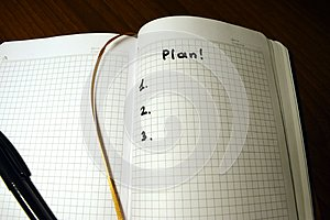 Three-point plan, schedule - а notepad in a cage on a wooden background and the inscription with a black marker `plan 1, 2, 3`