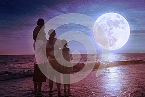 Family standing on beach and watching the moon.Celebrate Mid-autumn festival