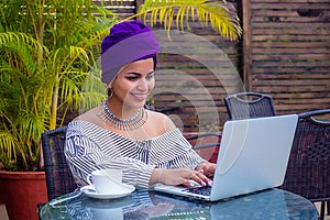 Smiling beautiful indian girl with ethnic turban on head culture working on laptop outdoors summer cafe