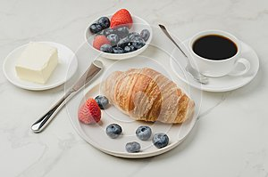 Delicious breakfast with fresh coffee, fresh croissants and berries. Selective focus