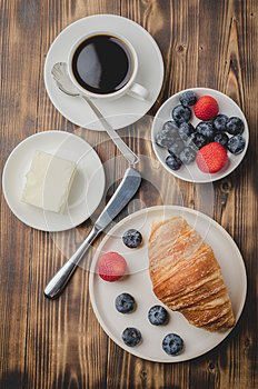 Coffee cup, croissant with berries in white bowl and butter knife on wooden table. Top view. Healthy breakfast with fresh berries