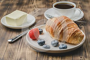 Coffee hous cup, croissant with berries in white bowl and butter on wooden background. Healthy breakfast with fresh berries