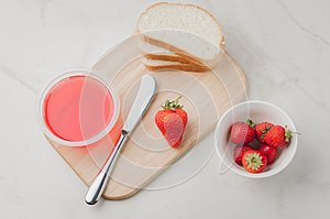 Strawberry jam. Making sandwiches with strawberry jam. Top view. Bread and strawberry jam on a white table with jar of jam and