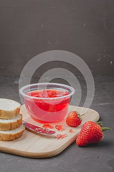 Strawberry jam. Bread and strawberry jam on a dark stone background with jar of jam and fresh strawberry. Making sandwiches with