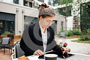Business lady sitting on veranda in coffee shop while working by digital social media project on tablet computer. Young creative f