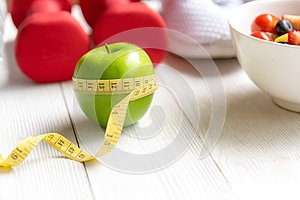 Diet and Healthy life loss weight Concept. Green apple and Weight scale measure tap with fresh vegetable and sport equipment for w