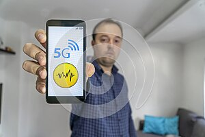 Man showing a smartphone with 5g danger sign on it