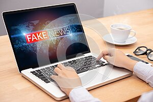 People reading fake news or HOAX on internet content via laptop.