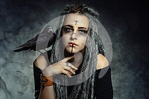 Portrait of a young woman with dreadlocks and with a raven