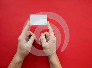 Female hands holding blank white business card on red background