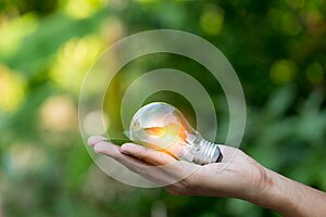 Hand holding light bulb,energy sources for renewable,natural energy concept