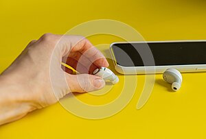 Hand Smartphone white wireless headphones on a bright yellow background