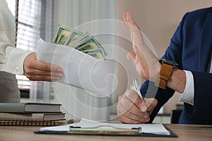 Businessman rejecting bribe at table in office, closeup