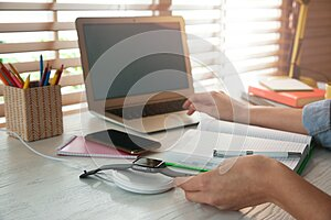 Woman putting smartwatch onto wireless charger at white wooden table, closeup. Modern workplace accessory