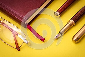 Stylish office still life on yellow table with pen, glasses and notepad