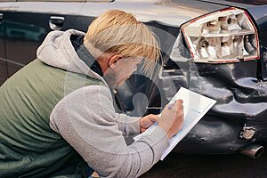 The guy fills out an insurance claim form after the accident