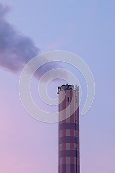 Chimney of an incineration plant, dawn windy morning