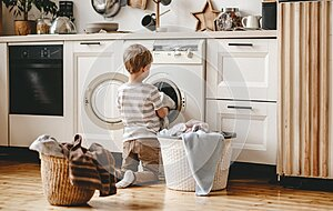 Anonymous   householder child boy in laundry   with washing machine