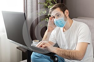 Young caucasian gloomy man in stress working from home office wearing protective mask using laptop and internet. Coronavirus covid