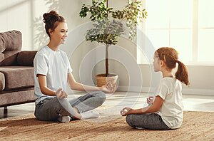 Mother and daughter meditating in living room