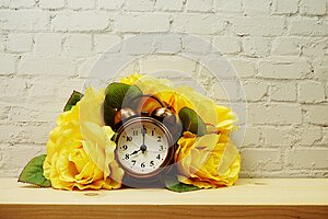 Alarm clock with flower decorative on white brick wall background