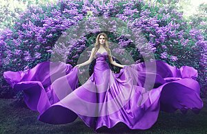 Fashion Model in Lilac Flowers, Young Woman in Beautiful Long Dress Waving on Wind, Outdoor Beauty Portrait in Blooming Garden