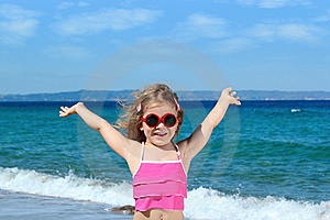 Little girl with sunglasses on the beach