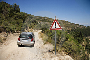 Car on dirt road with caution sign.