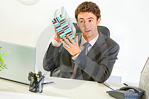 Interested businessman shaking present box