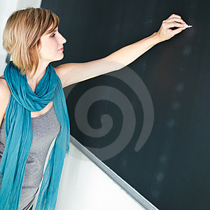 Young student writing on the blackboard
