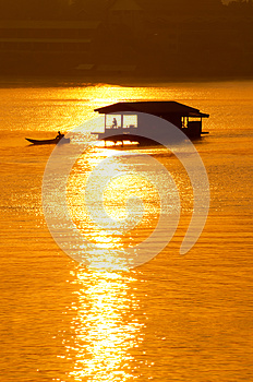 Sunset and boat with floating house