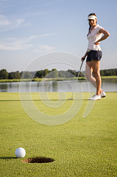 Girl golf player putting on green.