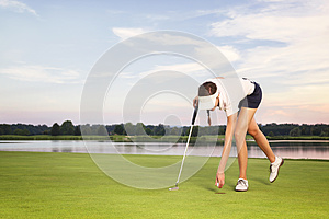 Girl golf player picking up ball from cup.
