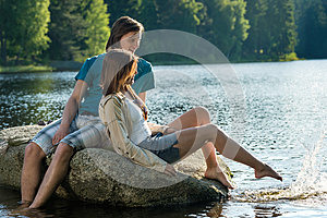 Couple sitting on rock sharing romantic moment
