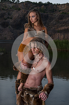 Primitive man holds his woman in his arms on lake background
