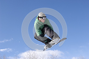 Snowboarder Performing Stunt Against Blue Sky
