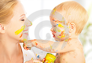 Happy dirty baby draws paints on her face of mother