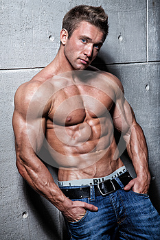 Muscular young guy posing in jeans and bare-chested