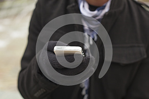Mobile phone in hands with glowes, cold weather