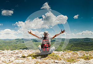 Man greeting nature on the top of mountain