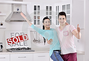 Happy Couple in Front of Sold Real Estate Sign