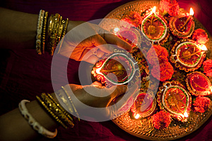 Hands holding Diwali lamps